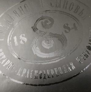 ant matinių tamsių paviršių šriftas ir ornamentika atspausdinta šilkografijos technologija blizgiu UV laku